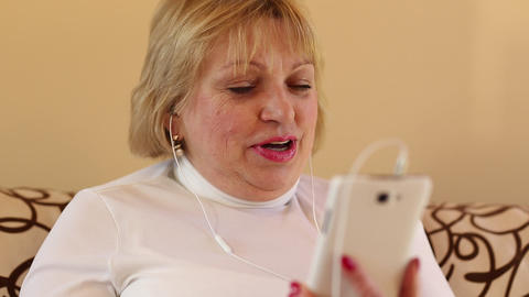 Senior woman with white smartphone talks sits on the sofa Footage
