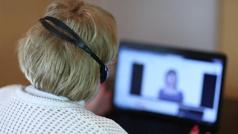 Woman with headphones on computer talks to a client via computer Live Action