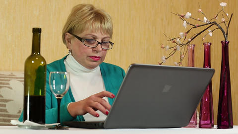 Woman with a bottle of wine sits at a table and types text on laptop Footage