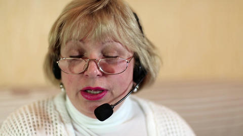 Woman with headphones with microphone looks at the camera and talks to a client Footage
