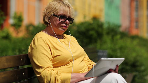 Woman in yellow jacket using tablet computer. Woman holding pad with headset Live Action