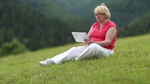 Woman sits on a green grass and uses tablet computer Footage