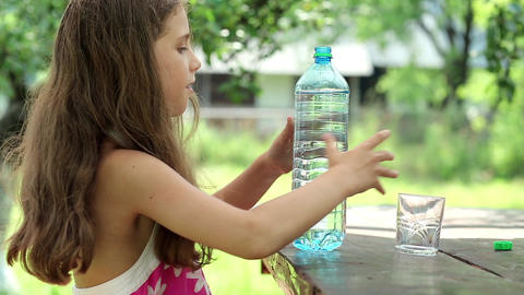 Girl pours water from a bottle into a glass Footage