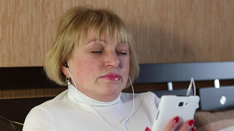 Blonde woman with white smartphone sits on the bed and listens to music Footage
