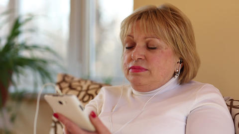 Blonde woman with white smartphone sits on the couch and listens to music Footage