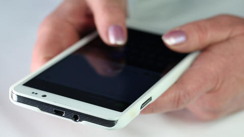 Closeup of woman hands with white cell phone. Woman typing sms on her smartphone Footage