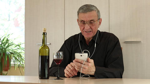 Man with cell phone sits at the table and drinks wine Footage