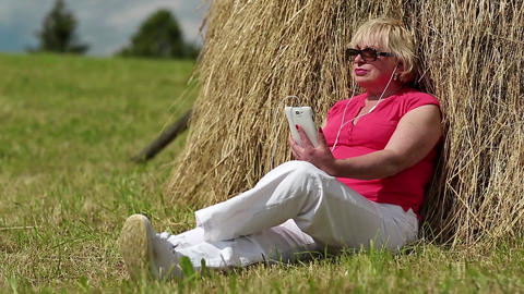 Woman with white smartphone sitting near haystack and listening to music Footage