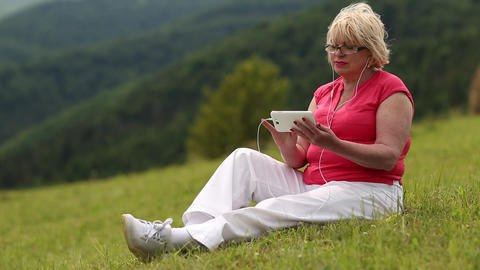 Woman sits on a green grass and uses smartphone Footage