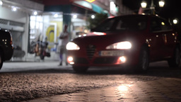 Car passing on the street dark with headlights on besides a shop lit 3 Footage
