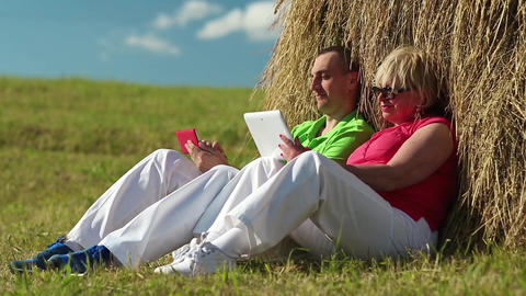 Man with red smartphone and woman with tablet computer sits near a hayrick Footage