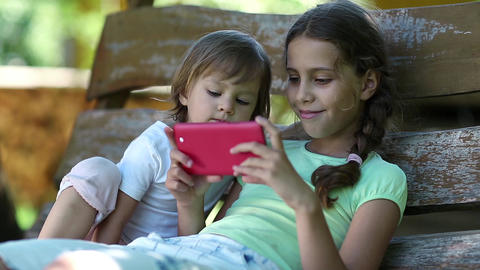 Two little girls with red smartphone sits on the swing bench Footage