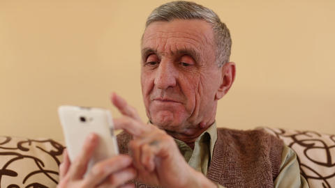 Senior man looking and flipping through the photos in her smartphone Footage