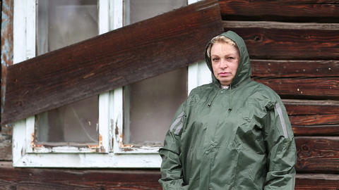 Woman in waterproof raincoat stands near uninhabited house Footage