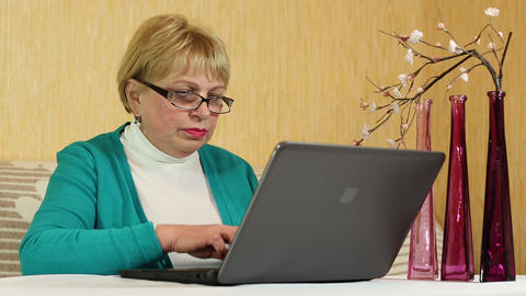 Woman with notebook. Senior woman types text using laptop Footage