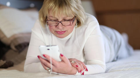 Woman with white smartphone lying on the bed and listening to music Footage