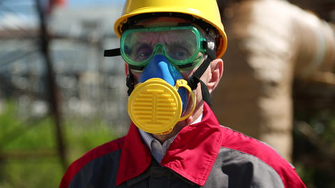 Repairman in hard hat, goggles and respirator at industrial area Footage