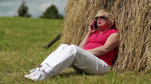 Woman sits near haystack and communicates via mobile phone Footage