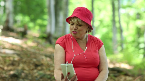Woman sits on a fallen tree in the forest and communicates via smartphone Footage