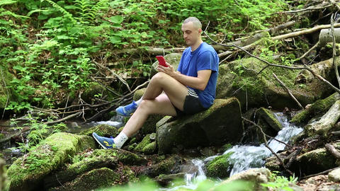 Man with mobile phone sits near small river in the forest Footage