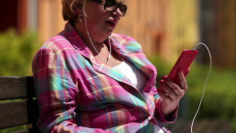 Woman sits on the bench and communicates via smartphone Footage
