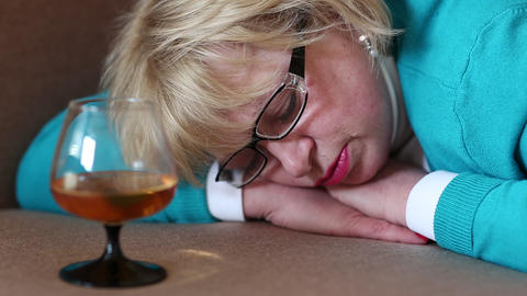 Sleeping woman lying on sofa with a glass of cognac Footage