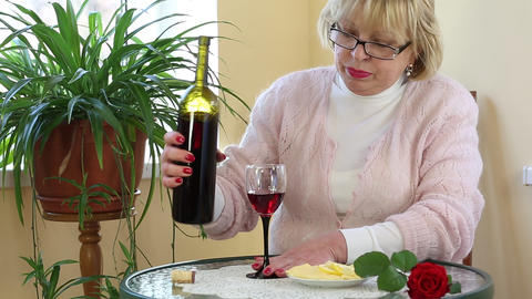 Woman sits at a table and drinks red wine Footage