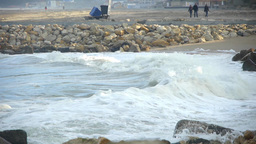Sea waves that break the rocky shore, while three friends walking on beach sand  Footage