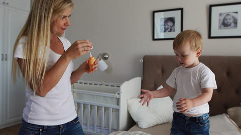 Caring mother plays son looking at soap bubbles, the boy is happy jumping on the Footage