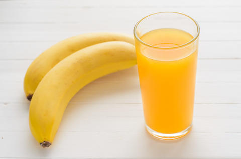 Glass of multifruit juice and two bananas on a white wooden table フォト