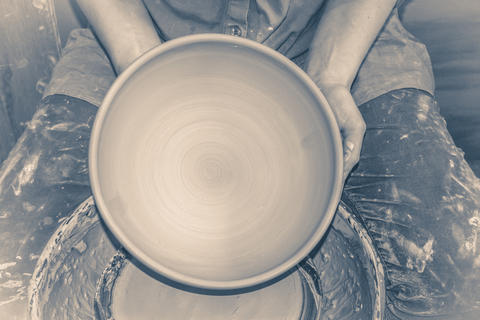 Photo in old vintage style. Master Potter holds half round clay plate フォト