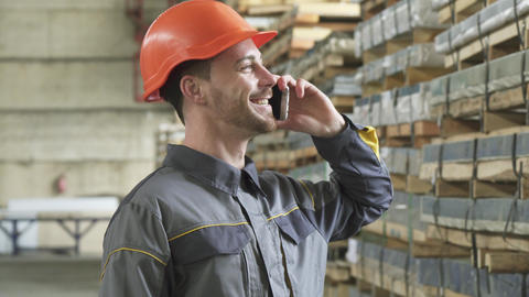 Happy factory worker in a hardhat smiling talking on the phone Footage