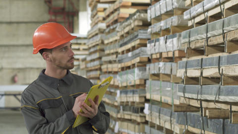 Handsome male warehouse worker walking writing on his clipboard Footage
