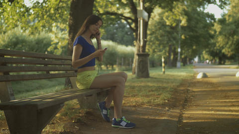 Jogging woman setting music on mp3 player before run Footage