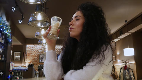 Inspired Lady with curly hair in a restaurant is drinking coffee and smile Live Action