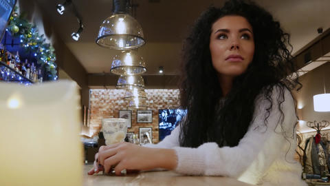 Beautiful curly-haired girl is waiting in the restaurant Footage