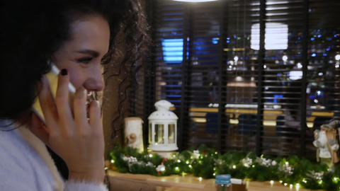 Happy girl with curly hair in a restaurant is talking on... Stock Video Footage