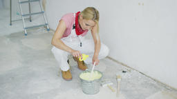 Woman mixing wall paint in bucket ビデオ