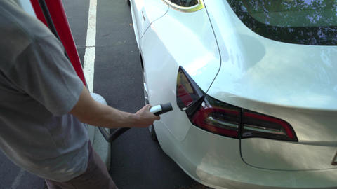 Person charging a Tesla Model 3 at a Tesla Supercharger station in Raleigh, NC Live Action