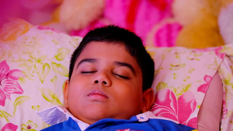 Young boy sleeps peacefully on bed, focus shift Live Action