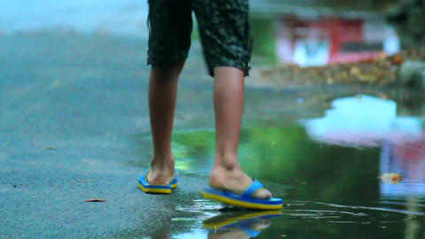 Low angled shot of small boy walking in the street just after the rain Footage