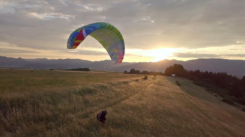 Playing with paraglider in golden meadow at sunset ビデオ