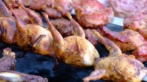 A close view of well-cooked quail meat on skewers, lying on a brazier ビデオ