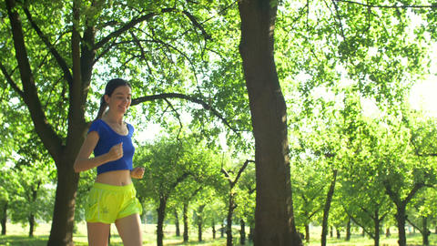 Smiling beautiful sporty woman jogging in park Footage