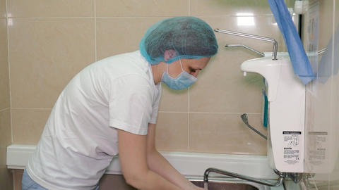 Surgeon getting ready for the cosmetic surgery. Doctor washing his hands before Footage
