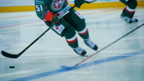 slow motion players of opposite teams stickhandle puck Live Action