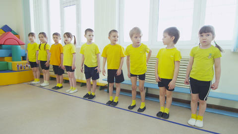 children in yellow stand in line at PT lesson in preschool Footage