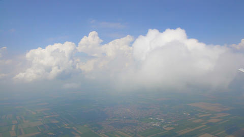 Clouds floating in sky over fields below, view from airplane, weather forecast Live Action