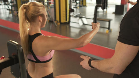Trainer helping young woman to do chest fly workout, correcting arms movement Footage