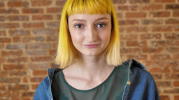 Young charming woman with yellow hair looking at camera and standing near brick Footage